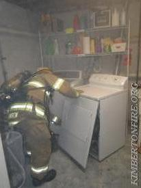 Firefighter Jorgensen removes front cover to get inside Dryer where the fire started.