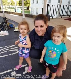 Firefighter-EMT Ashley Marchetti poses with two new friends from the visit.
