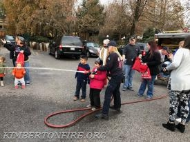 Firefighter Samantha Gable works with the children as they take turns with the fire hose.