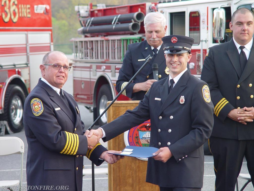 Fire Chief Jay Pollinger (left) hands Tyler his certification